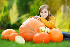 Adorable little girl having fun on a pumpkin patch Stock Image