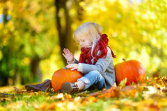 Adorable little girl having fun on a pumpkin patch on beautiful autumn day Stock Image