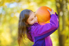 Adorable little girl having fun on a pumpkin patch on beautiful autumn day Stock Photo