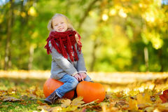 Adorable little girl having fun on a pumpkin patch on beautiful autumn day Royalty Free Stock Photo