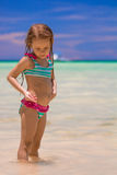 Adorable little girl having fun at shallow water. Happy little girl having fun and jumping at shallow water Stock Images