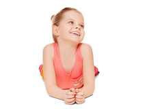 Adorable little girl having fun smiling is lying looking to the side, isolated on white background Royalty Free Stock Images
