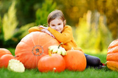 Adorable little girl having fun together on a pumpkin patch Stock Photos