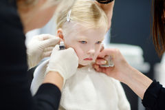Adorable little girl having her ears pierced Royalty Free Stock Photography