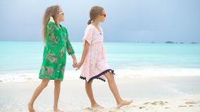 Adorable little girl having a lot of fun at tropical beach playing together background turquiose water and blue sky. Little girls having fun at tropical beach stock footage