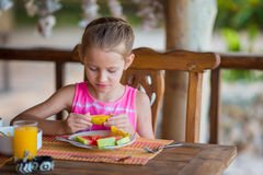 Adorable little girl having lunch at outdoor cafe Stock Image