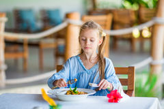 Adorable little girl having lunch at outdoor cafe Stock Photo