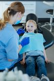 Adorable little girl having oral cavity checkup done. Proper teeth care. Cute little girl sitting in a dentist chair and having oral cavity checkup done by a Royalty Free Stock Photo