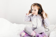 Adorable little girl in headphones enjoy with a music. Stock Images