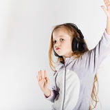 Adorable little girl in headphones enjoy with a music. Royalty Free Stock Photos