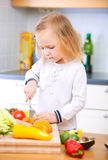 Adorable little girl helping at kitchen Stock Photo