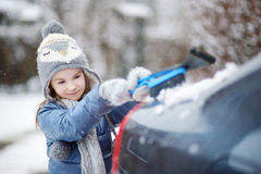 Adorable little girl helping to brush a snow Royalty Free Stock Photo