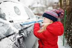 Adorable little girl helping to brush a snow from a car. Mommy`s little helper. Winter activities for kids royalty free stock photos
