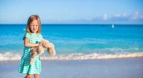 Adorable little girl with her bunny toy on tropical beach vacation Royalty Free Stock Images