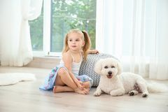 Adorable little girl with her dog. At home stock images