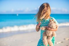 Adorable little girl with her favorite toy on tropical beach vacation Stock Photos
