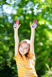 Adorable little girl with her hands painted having fun outdoors. On bright summer day stock photos