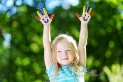 Adorable little girl with her hands painted having fun outdoors. On bright summer day stock photography