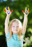 Adorable little girl with her hands painted having fun outdoors. On bright summer day royalty free stock photo