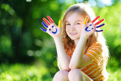 Adorable little girl with her hands painted having fun outdoors. On bright summer day stock photo