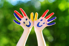 Adorable little girl with her hands painted having fun outdoors. On bright summer day royalty free stock image