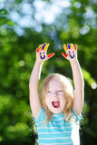 Adorable little girl with her hands painted having fun outdoors. On bright summer day royalty free stock photography