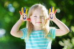 Adorable little girl with her hands painted having fun outdoors. On bright summer day royalty free stock images
