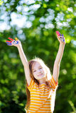 Adorable little girl with her hands painted having fun outdoors. On bright summer day stock images