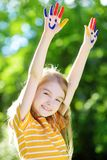 Adorable little girl with her hands painted having fun outdoors. On bright summer day royalty free stock photos