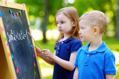 Adorable little girl and her little student Royalty Free Stock Images