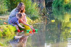 Adorable little girl and her mom playing with paper boats in a r Royalty Free Stock Photos