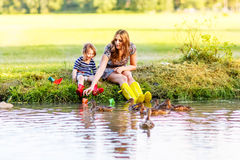 Adorable little girl and her mom playing with paper boats in a r Stock Images