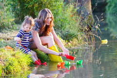 Adorable little girl and her mom playing with paper boats in a r Stock Image