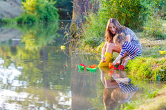 Adorable little girl and her mom playing with paper boats in a r Royalty Free Stock Photo