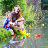 Adorable little girl and her mom playing with paper boats in a r Stock Photo