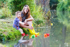 Adorable little girl and her mom playing with paper boats Stock Images