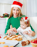 Adorable little girl with her mother baking Christmas cookies Royalty Free Stock Photo