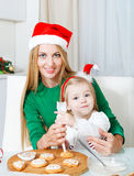 Adorable little girl with her mother baking Christmas cookies Stock Images