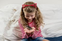 Adorable little girl with her pet - small hamster. Adorable little girl with her pet - a small hamster Stock Photography