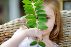 Adorable little girl hiding behind a leaf Royalty Free Stock Images
