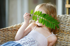 Adorable little girl hiding behind a leaf Stock Photo