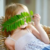 Adorable little girl hiding behind a leaf Stock Photos