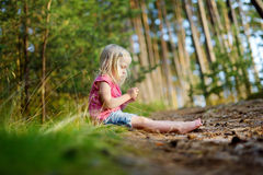 Adorable little girl hiking in the forest on summer day Royalty Free Stock Image