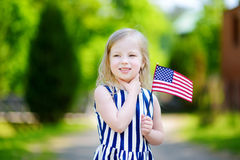 Adorable little girl holding american flag outdoors on beautiful summer day Royalty Free Stock Images