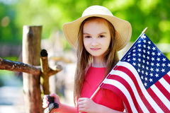 Adorable little girl holding american flag outdoors on beautiful summer day. Independence Day concept Stock Photo