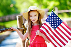 Adorable little girl holding american flag outdoors on beautiful summer day Royalty Free Stock Image