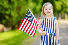 Adorable little girl holding american flag outdoors on beautiful summer day Stock Images