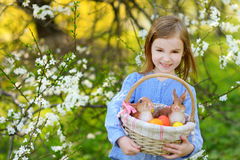 Adorable little girl holding a basket of Easter eggs on Easter day. Adorable little girl holding a basket of Easter eggs in blooming spring garden on Easter day Stock Photo