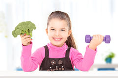 Adorable little girl holding broccoli and a dumbbell Stock Images