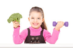 Adorable little girl holding broccoli and a dumbbell, seated at Stock Images